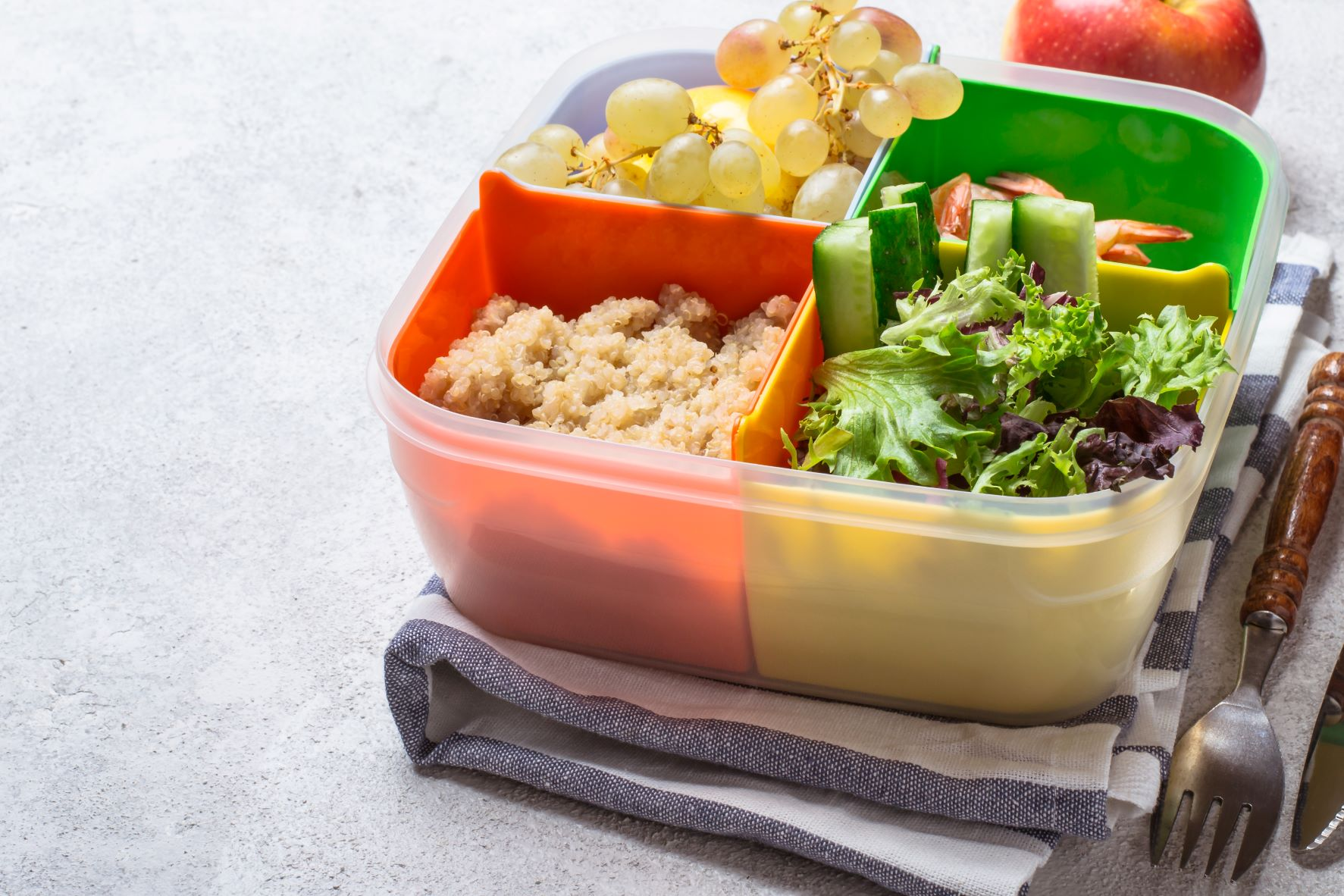 Das Bild zeigt eine gefüllte Essensbox mit Salat, Weintrauben und anderen Beilagen.
