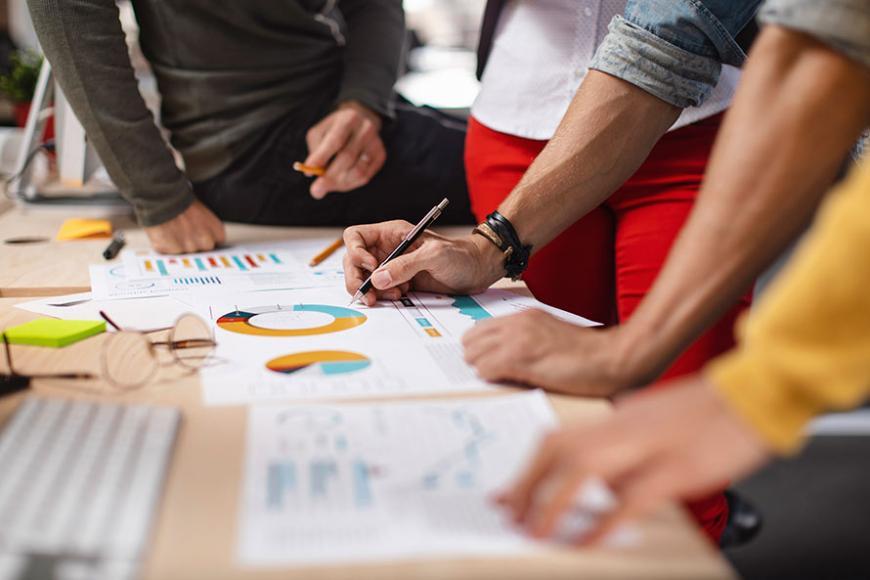 Das Bild zeigt die Hände und Arme mehrerer Personen, die gemeinsam über einen Schreibtisch gebeugt Dokumente sichten und Notizen machen.