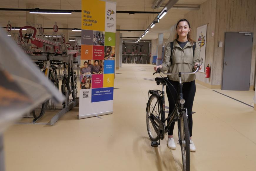 Eine Studentin mit Fahrrad in einem Fahrradparkhaus.