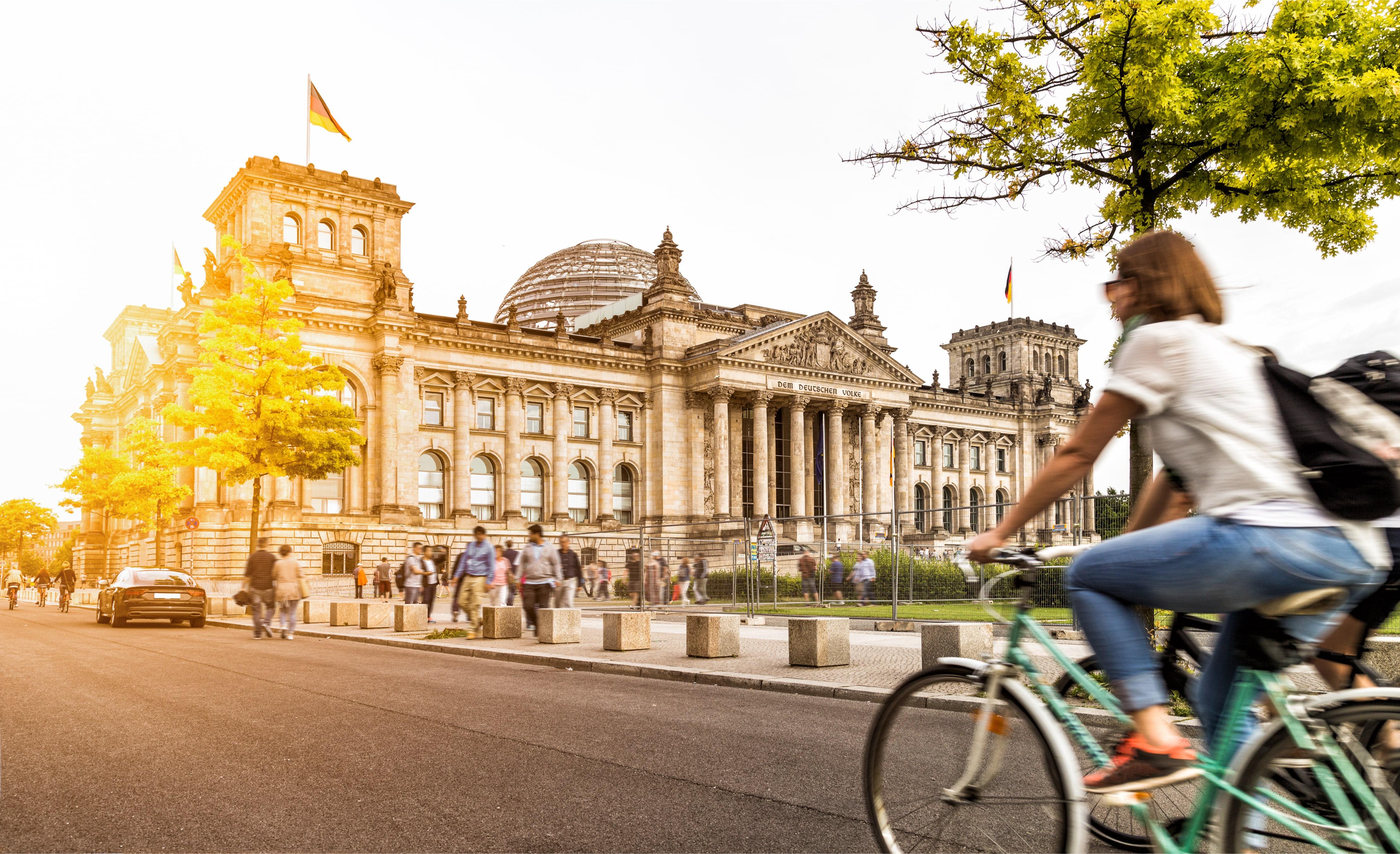 Fahrradfahrerin in Berlin, im Hintergrund ein Regierungsgebäude